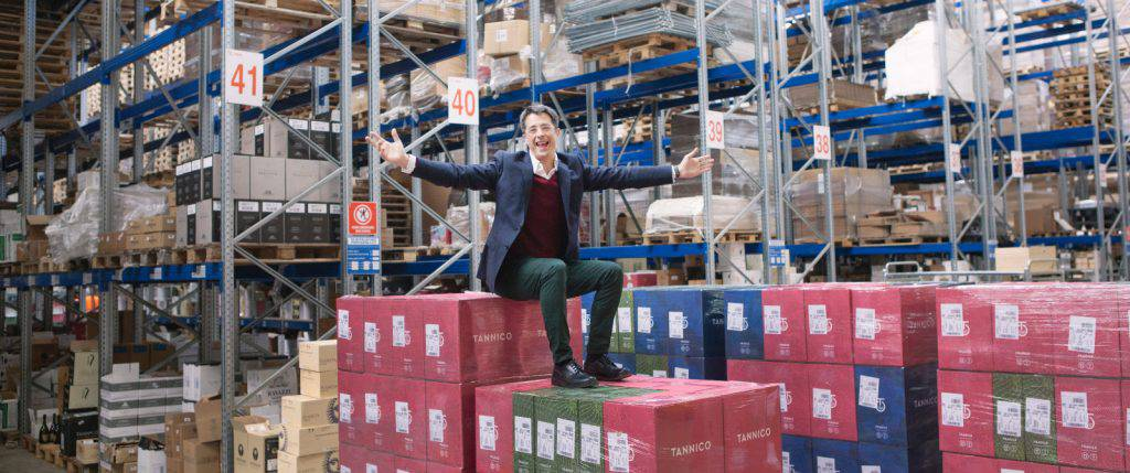 A man sitting on boxes and spreading hands in a large warehouse
