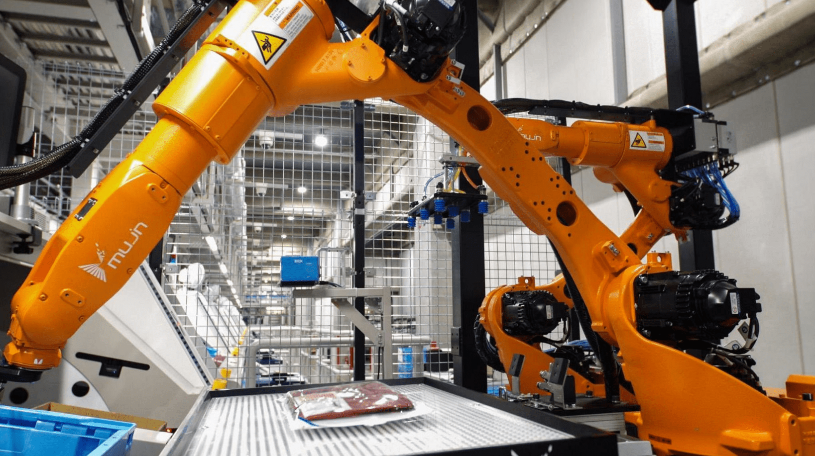 An orange Mujn robot and a folded t-shirt in a factory