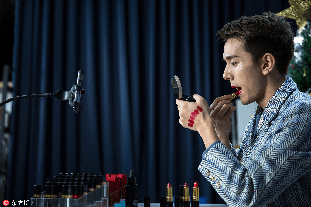 Image showing a man trying out different shades of lipstick.