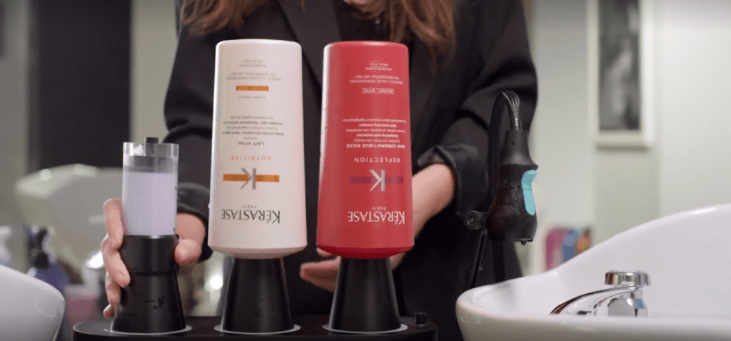 L'Oreal's water-saving rinsing solution shown with hair products in a salon.