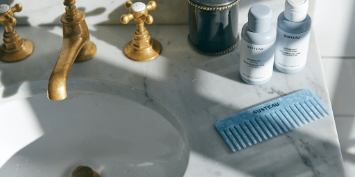 """Image of a sink showing Susteau's """"waterless"""" haircare products alongside it."""